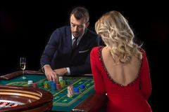 A beautiful young woman and a man are sitting at a roulette table. Casino. Royalty Free Stock Image