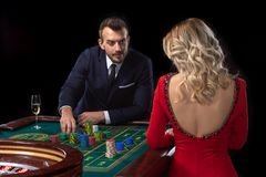 A beautiful young woman and a man are sitting at a roulette table. Casino. Royalty Free Stock Photography
