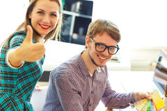Beautiful young woman and man with thumb up in office Stock Photos