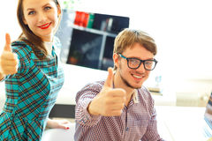 Beautiful young woman and man with thumb up in office Royalty Free Stock Images