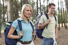 Beautiful young woman with man trekking in forest Royalty Free Stock Images