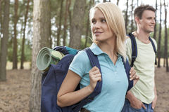 Beautiful young woman with man trekking in forest Stock Image