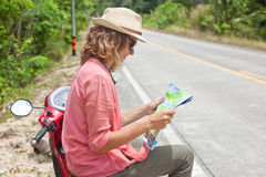 Beautiful young woman with map in hand and a motorbike on the ro Royalty Free Stock Photo
