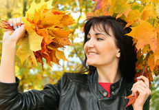 Beautiful young woman with maple leaves in autumn park Stock Photo