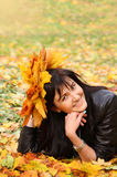 Beautiful young woman with maple leaves in autumn park Stock Photography