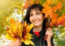 Beautiful young woman with maple leaves in autumn park Royalty Free Stock Photo