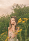 Beautiful Young Woman in Meadow of Flowers. Royalty Free Stock Photography