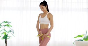 Beautiful young woman measuring her hip. Weight loss concept