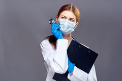 Beautiful young woman in medical mask and lab coat holds documents on dark gray background, doctor, medicine.  Stock Photos