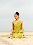Beautiful young woman meditating at the beach Stock Image