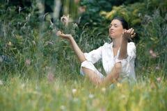 Beautiful young woman meditating on field Stock Photos