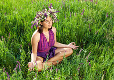 Beautiful young woman meditating in meadow Royalty Free Stock Photography