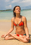 Beautiful young woman meditating by the ocean stock photo