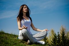 Beautiful young woman meditating on a patch of Royalty Free Stock Photography