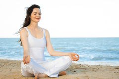 Beautiful young woman meditating. Peaceful healthy & fit young woman meditating on the beach Royalty Free Stock Image