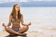 Beautiful young woman meditation on seacoast Royalty Free Stock Photography