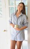 Beautiful young woman in men's shirt with coffee cup Stock Image