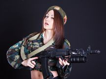 Beautiful young woman in a military uniform with an assault rifl Stock Photos
