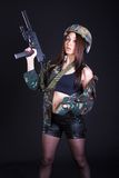 Beautiful young woman in a military uniform with a submachine gu Royalty Free Stock Photography