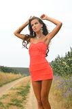 Beautiful young woman in mini dress standing on. Picture of beautiful young lady in mini coral dress standing on summer countryside road. Pretty girl with raised royalty free stock photo
