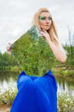 Beautiful young woman with a mirror at the countryside Stock Photography