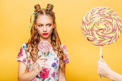 Stylish girl in summer colorful dress. Beautiful young woman with mistrustful look holds in hand big lollypop. Somebody gives one more candy to girl, studio Stock Image