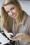 Beautiful young woman on mobile phone. A blonde student hodling her mobile phone Royalty Free Stock Images
