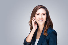 Beautiful young woman with mobile phone making a phone call. On grey background Royalty Free Stock Photos