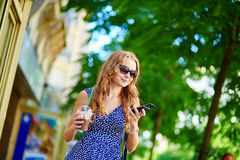 Beautiful young woman with mobile phone. In the street on a summer day Stock Photos