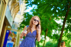 Beautiful young woman with mobile phone. In the street on a summer day Stock Images