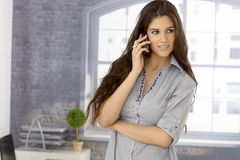 Beautiful young woman on mobilephone. Beautiful young woman talking on mobilephone, looking away Royalty Free Stock Photos