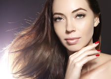 Beautiful young woman model with flying brown color hair. . Make up, curly hairstyle. Haircare, make-up. Royalty Free Stock Image