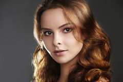 Beautiful young woman model with flying brown hair. Beauty with clean skin, fashion makeup. Make up, curly hairstyle Royalty Free Stock Photography