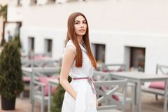 Beautiful young woman model in a stylish white dress royalty free stock image