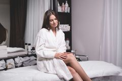 Beautiful young woman in a modern beauty salon showing her perfect slim legs stock images
