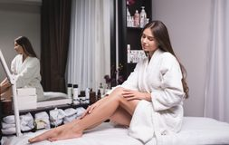 Beautiful young woman in a modern beauty salon showing her perfect slim legs stock image