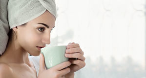 Beautiful young woman with morning cup of hot beverage. Royalty Free Stock Images