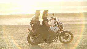 Beautiful young woman motorcyclist with his girlfriend riding a motorcycle in a desert on sunset or sunrise. Two woman on a bike. stock footage
