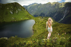 Beautiful young woman in the mountains. Beautiful young woman with red hair standing on a rock and looking at the lake Stock Images