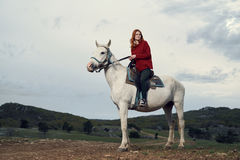 Beautiful young woman in the mountains walking with her horse Royalty Free Stock Images