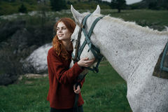 Beautiful young woman in the mountains walking with her horse Royalty Free Stock Image