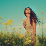 Beautiful young woman moving and posing in the rapeseed field Royalty Free Stock Images