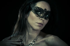 Beautiful young woman in mysterious black Venetian mask Royalty Free Stock Photos