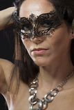 Beautiful young woman in mysterious black Venetian mask Stock Photos