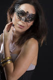 Beautiful young woman in mysterious black Venetian mask Stock Photo