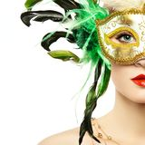 Beautiful young woman in mysterious golden Venetian mask royalty free stock photos