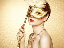 Beautiful young woman in mysterious golden Venetian mask. Fashion photo Stock Image