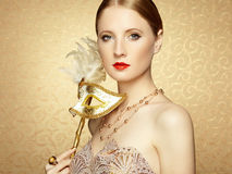 Beautiful young woman in mysterious golden Venetian mask. Fashion photo Stock Images