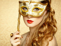 Beautiful young woman in mysterious golden Venetian mask. Fashion photo Royalty Free Stock Image