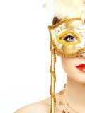 Beautiful young woman in mysterious golden Venetian mask Stock Photo